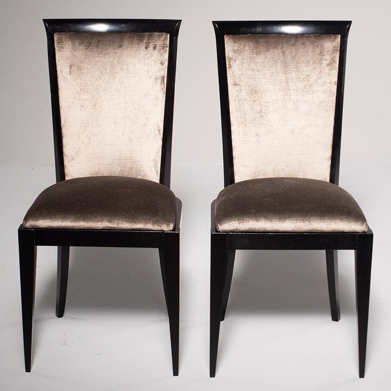 This set of circa 1960s eight dining chairs had a new ebonized finish professionally applied in England and have been reupholstered in a medium taupe colored chenille velvet. The fabric has a bit of sheen and the frames have subtle, elegant curves