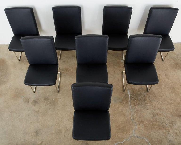 Stylish set of eight Thayer Coggin for Milo Baughman 1187 thin line dining chairs featuring a polished steel chrome finish. All the chairs have been recently reupholstered with a black leatherette naugahyde fabric. Beautifully crafted with the
