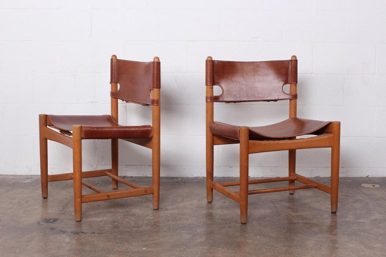 A set of six side chairs and two armchairs in oak and original patinated leather by Børge Mogensen.