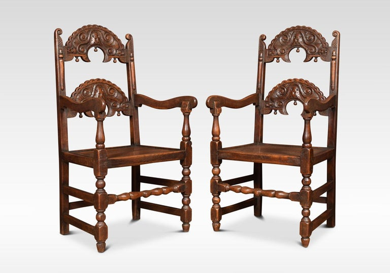 Comprising off a set of six chairs and two similar armchairs. Having arched supports with acorn drop finials above solid oak seats. All raised up on turned supports united by stretchers.