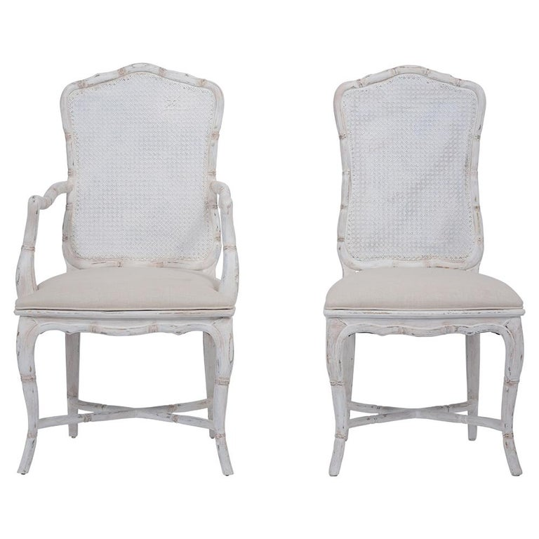 Set of Eight Provincial Dining Room Chairs handcrafted out of maple wood with its original caning that has been newly painted in an oyster color with a unique distressed finish. This set of eight features two armchairs & six side chairs with a faux