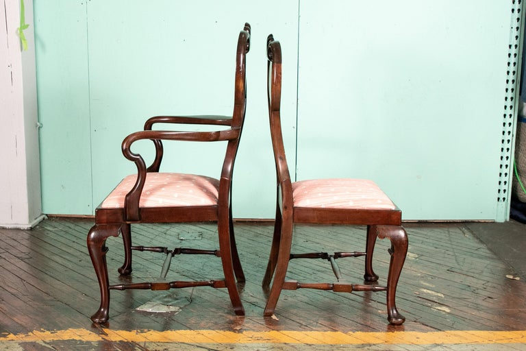 With very fine pronounced form and excellent proportions. Two arm and six side chairs. The splat backs with finely carved shells on the crests and shepherd's crook scrolled arms. Raised on cabriole legs in front with carved knees and pad feet,