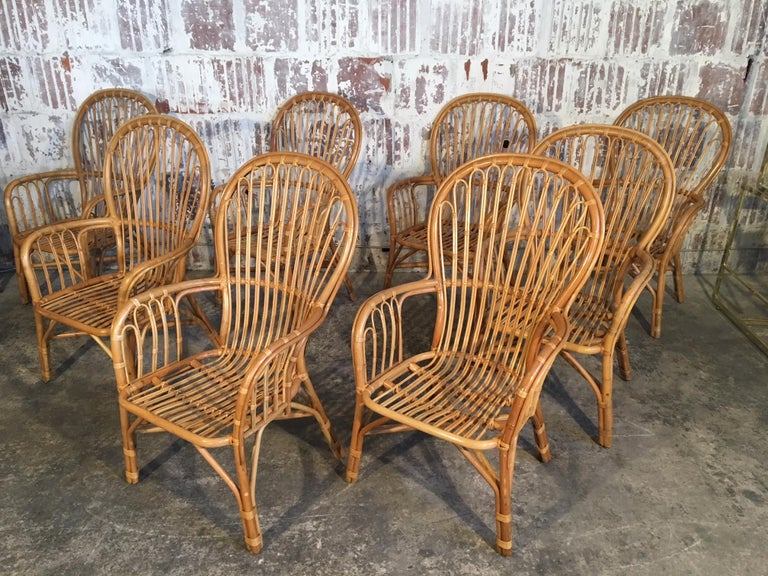 Set of 8 rattan fan-back arm chairs perfect for your tropical Palm Beach decor. Great example of midcentury bamboo furniture constructed by hand with craftsmanship that is no longer the norm. Some chairs are near perfect, others show abrasions