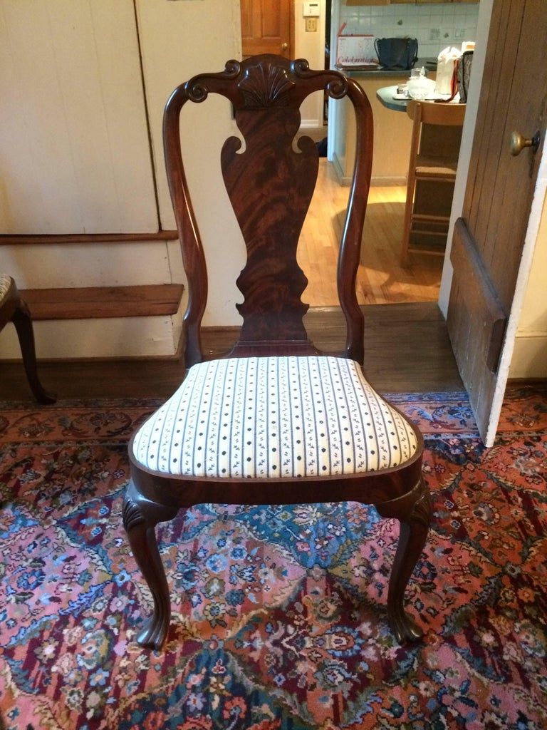 Beautiful carved mahogany dining chairs by Council Furniture having two armchairs and six side chairs, a pretty scallop shell decoration at the top and recently Scalamandre fabric covered seats. Measures: Sidechairs 24.5 W, 42.25 H, 33 D, 19.5 S/H.