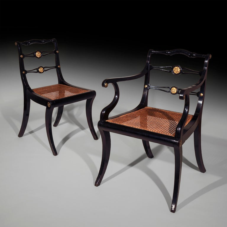 A fine set of eight (6+2) black lacquered and gilt-brass mounted dining chairs of Grecian-revival 'Klismos' form, by John Gee of London,  circa 1810.  With turned and curvedtop-rail above a pair of pierced mid-rails centred with gilt-brass 'English