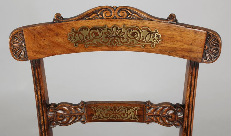 Set of eight Regency period simulated rosewood and brass inlaid chairs; the backs with carved lunette, foliate and scrolled decoration, and the overhanging top-rails and mid-rails with inlaid cut-brass arabesque panels on grounds of rosewood veneer.