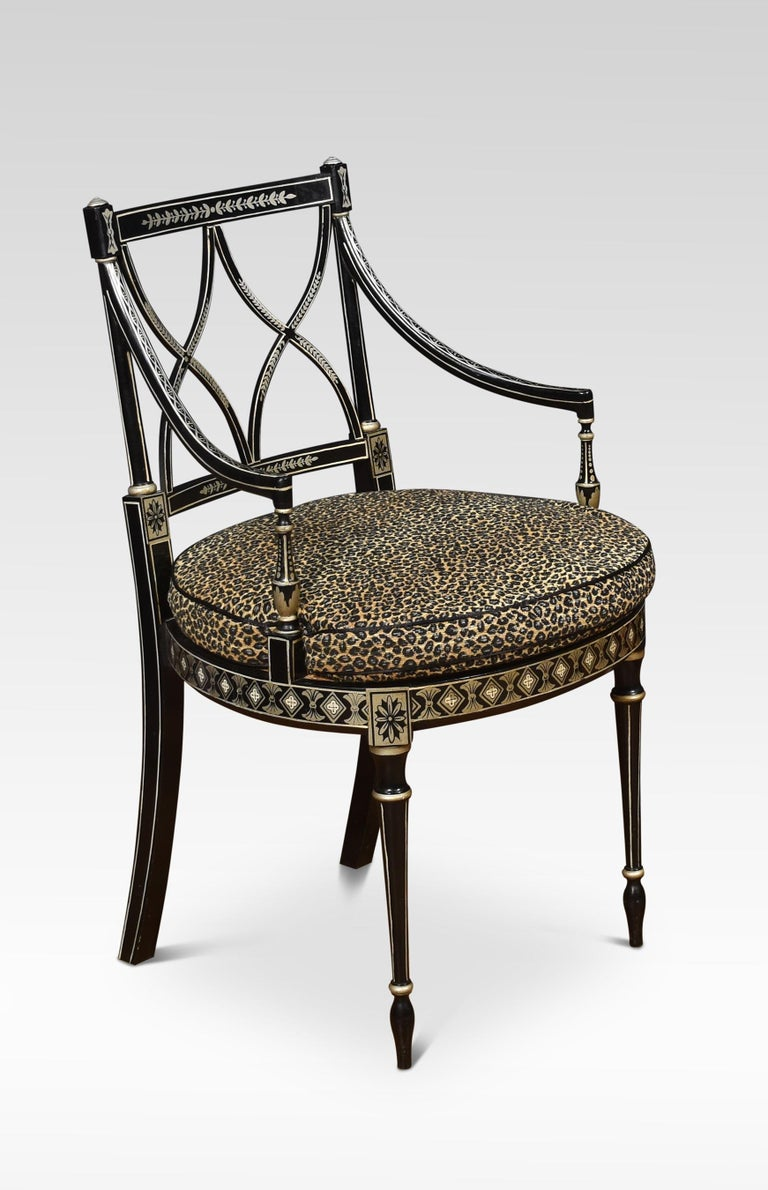 A set of eight Regency-style dining chairs with painted decoration on an ebonized ground. Above the berger seats having removable leopard skin print upholstered squab cushions enclosed by outswept arms. All raised up on turned tapering front