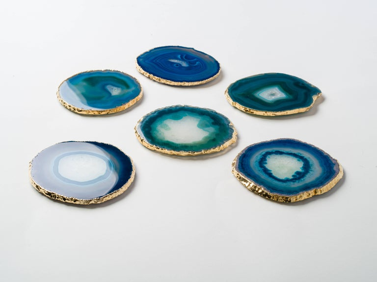 Stunning natural agate and crystal coasters with 24-karat gold plated edges. Polished fronts and natural rough edges. No two pieces are alike. Make beautiful accessories to any coffee table or dining table setting. Three color variations are