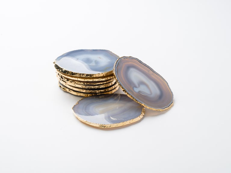 Stunning natural agate and crystal coasters with 24-karat gold-plated edges. Three color variations are available: Teal, onyx or grey. Polished fronts and natural rough edges. No two pieces are alike. Make beautiful accessories to any coffee table