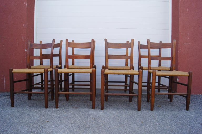 This set of eight dining chairs by the Cambridge, Massachusetts, furniture maker Charles Webb features solid teak frames with angled backs and rush seats.