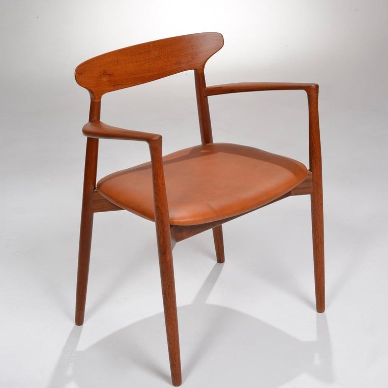 Set of 12 beautiful teak dining chairs - 10 side chairs and two with arms by Harry Østergaard for Randers Møbelfabrik, 1958.  Reupholstered in smooth cognac leather.