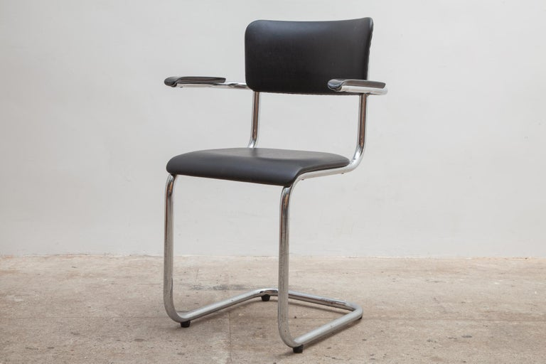 Seven chairs by Tubax, Belgium. Bent chrome frames with bakelite armrests. Black vinyl upholstery in excellent condition.  Dimensions: 55 W x 84 H x 42 D cm - Seat: 45 cm high.
