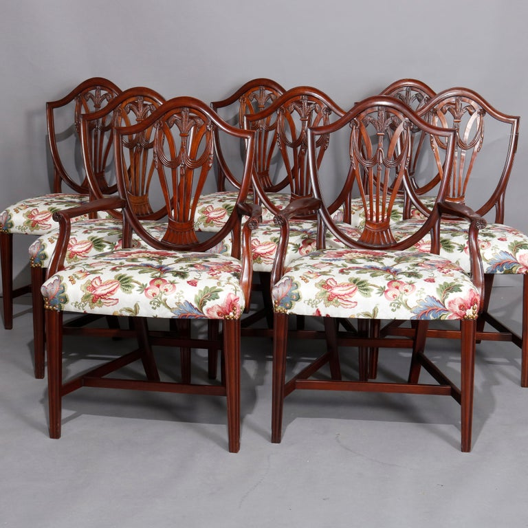 A vintage set of 8 English dining chairs offer mahogany frames with shield form backs with central carved fleur de lis palmette with flanking drape elements and upholstered seats, circa 1930  ***DELIVERY NOTICE – Due to COVID-19 we are employing
