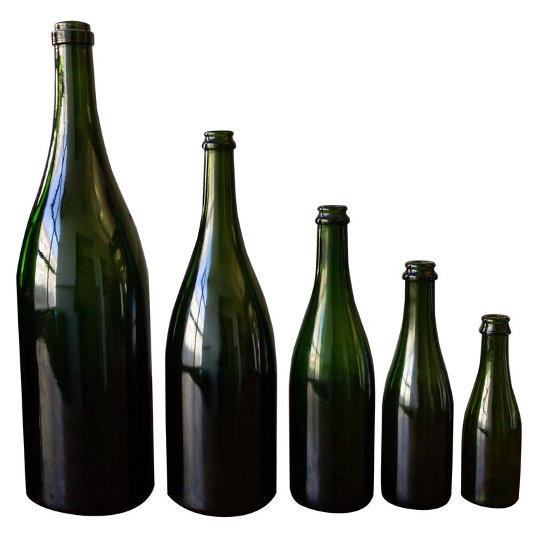 Grouping of eight vintage 1920s French champagne bottles in various sizes ranging from 7.5