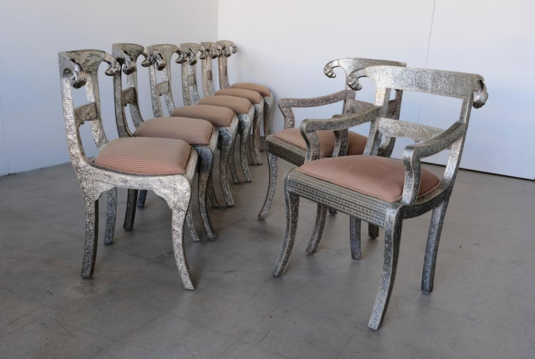 A set of eight Anglo-Indian handmade dining chairs. The chairs are embossed metal over wood finished with curved decorative cast Rams heads. The set consists of six side chairs and two captains chairs with arms. The metal respoussé has a floral and