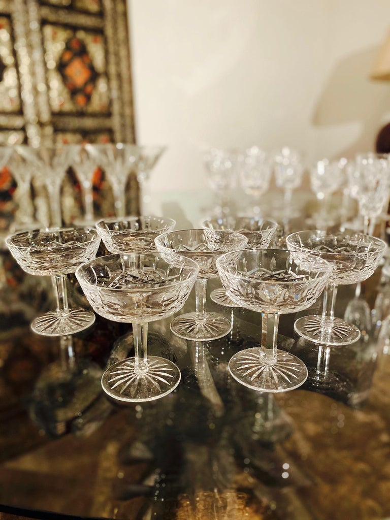 Set of eight luxury crystal coupe champagne glasses from Waterford Crystal. The Lismore Collection is perhaps Waterford's most distinguished design featuring handblown crystal with the pattern's signature diamond and wedge cuts. First introduced in