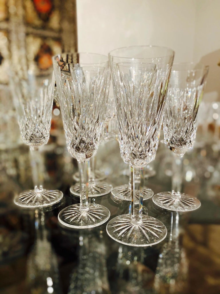 Set of eight luxury crystal champagne flutes from Waterford Crystal, circa 1995. The Lismore Collection is perhaps Waterford's most distinguished design featuring hand blown crystal with the pattern's signature diamond and wedge cuts. First