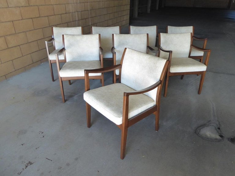 A gorgeous set of eight walnut dining chairs by Johnson Chair Co. These are all armchairs and are newly reupholstered in a beautiful nubby fabric that is most appropriate to the period and style. Commodious and comfortable these chairs are also