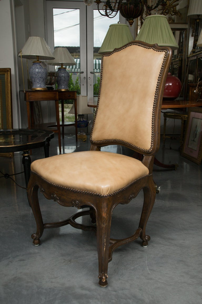 This is a sophisticated, yet mellow, set of eight walnut French Louis XV dining side chairs, the shaped top rail over a leather-upholstered back secured with brass nail heads, above a fully padded leather seat secured with brass nail heads over a