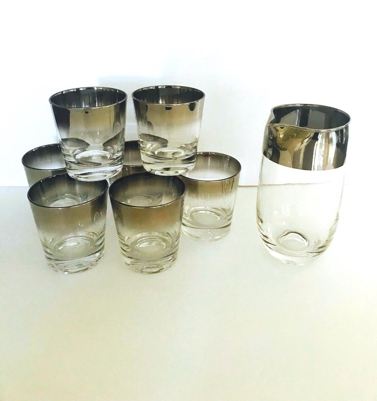 Iconic Mid-Century Modern barware set with silver fade overlay design. Set features 7 whiskey rock glasses and a sleek cylinder cocktail Shaker or martini mixer with spout. The glasses have tapered forms with gradient silver rims in hues of