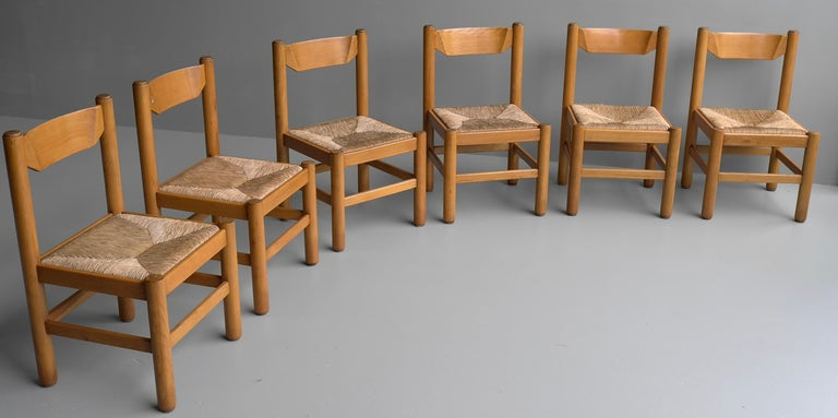 Set of eight wooden dining chairs in style of Charlotte Perriand, France, 1960 Solid heavy wooden chairs with cane or rush seats. The pictures shown only six chairs but we have 2 more. The listed price is for 8 pieces. We also have an identical set
