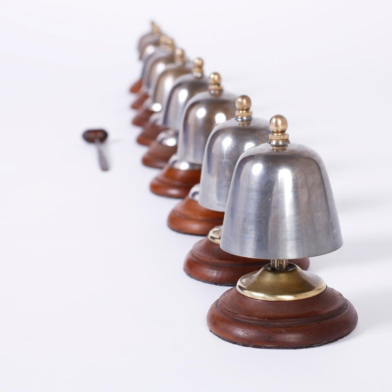 Intriguing antique set of nine bells crafted in steel with a crisp clear ring in the scale of a major. Featuring brass posts with Greek key designs, brass caps and finials, hand carved mallet and turned mahogany bases.  Bell heights range from 4.5