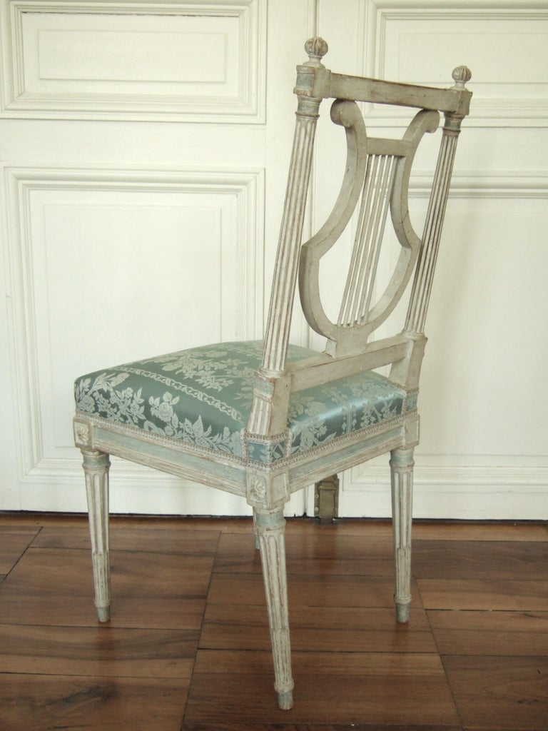 Exceptional series of Louis XVI lyre chairs in lacquered wood, a prized model and symbol of refinement in the 18th century. While these chairs are unstamped, their details are strongly reminiscent of a production by Jacob: finessed sculpture with