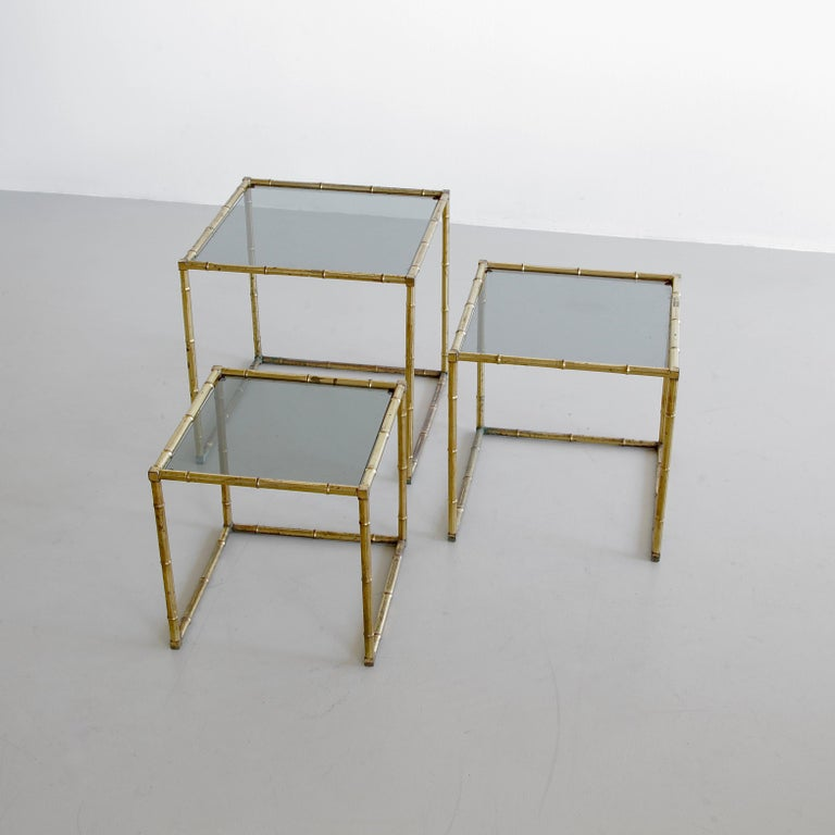Set of three side nesting tables. France, 1960s.  Faux bamboo frames with lightly green-tinted glass tops. The size indicated is for the largest of the set. Please enquire about the other measurements.