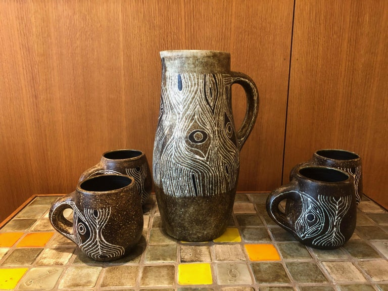 Set of five glazed ceramics (one pitcher and four mugs) by Les 2 Potiers (Michelle and Jacques Serre), active in France between 1956 and 1970. Dimensions indicated below are for the pitcher. Dimensions of mugs are: H12 / D12 cm.