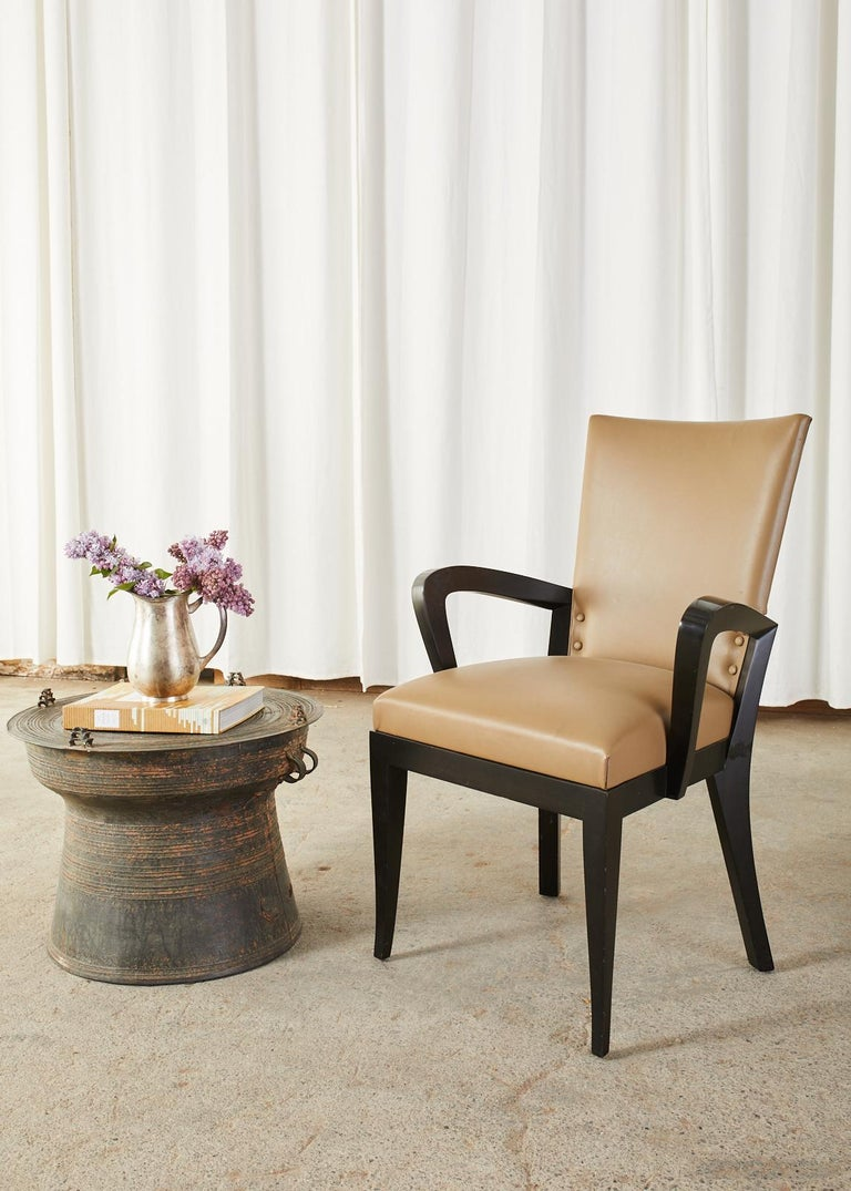 Dramatic set of five leather dining armchairs designed by Dakota Jackson known as Cadette chairs. They feature on an ebonized hardwood frame with gracefully curved arms that flare out like wings and saber style legs. The ergonomic frame has a curved