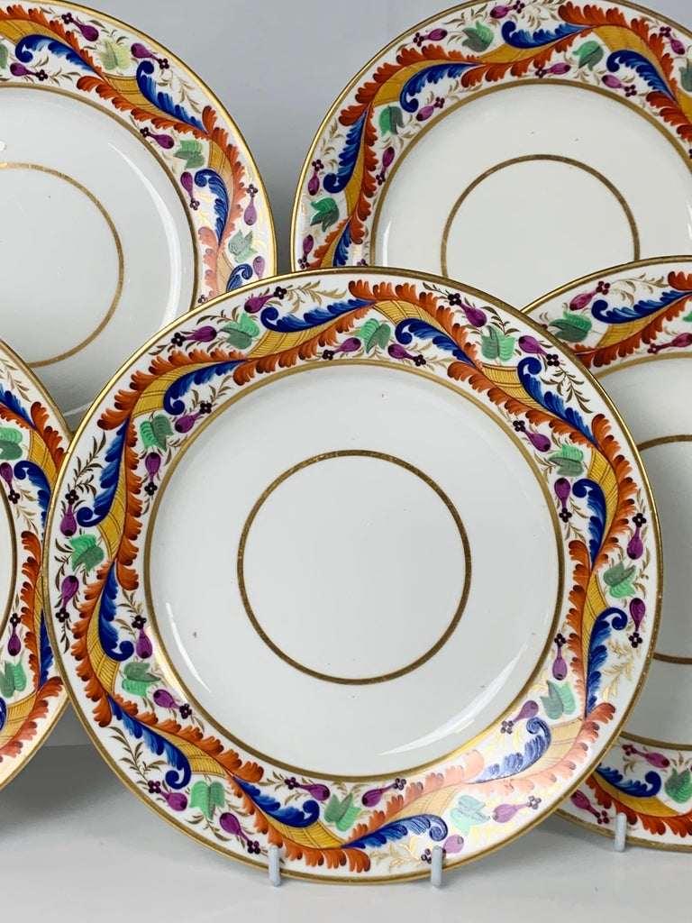 A set of five Derby dishes made in England, circa 1810. The brilliant colors of the border: red, orange, and blue combine in an exquisite vine-like pattern. The green flowers, gilded leaves, and small purple buds add to the colorful design. At the