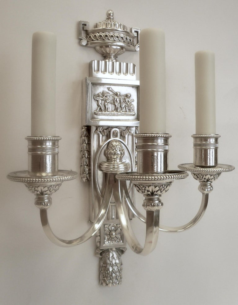 This handsome set of five Caldwell sconces feature neoclassical motifs including acanthus and laurel leaves, urns and swags, and Robert Adam style plaques with mythological scenes.
