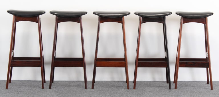 A fabulous set of five rosewood bar stools designed by Johannes Andersen manufactured by Brdr. Andersen Vejen Denmark, 1960s. These stools have the original faux leather upholstery. Very good condition with age appropriate wear.