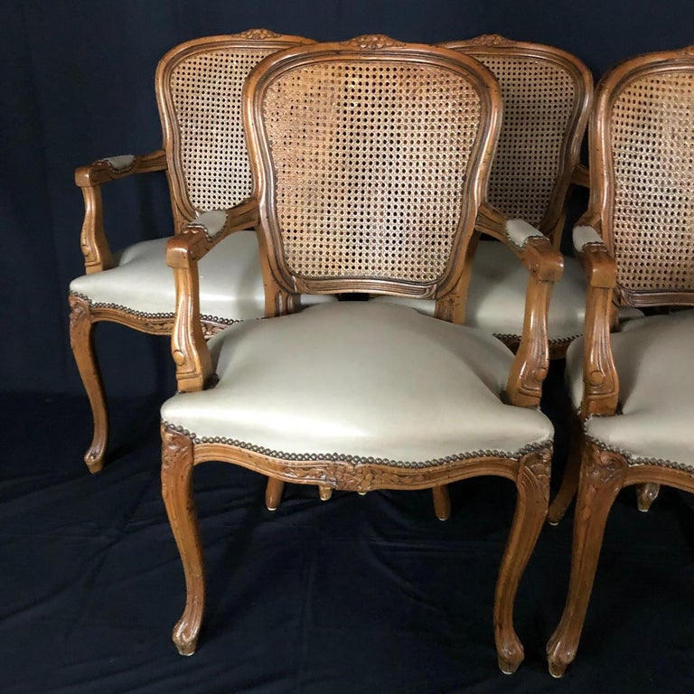 Really beautiful set of five walnut carved Louis XV style chairs with exquisitely carved backs, aprons and jabots over elegant curved cabriole legs. Brass tacks line the beige leather seats and armrests. Measure: Arm height 26.5 #5113.