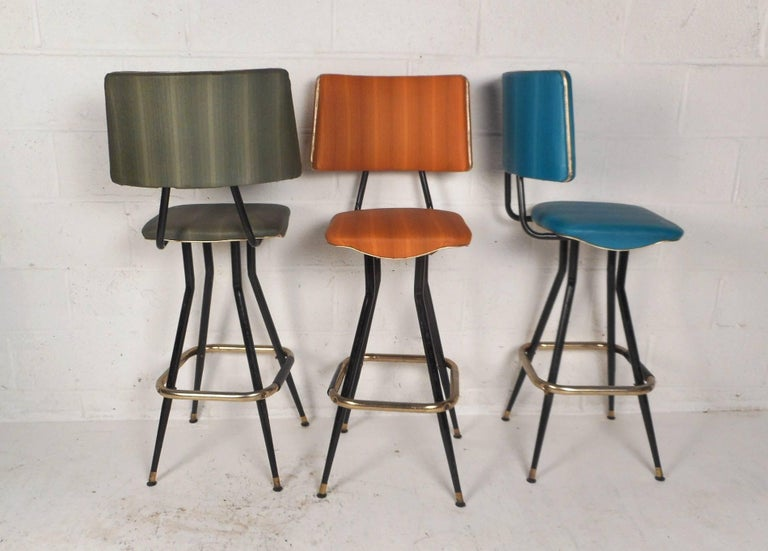 This stylish vintage modern set of five bar stools feature different colored upholstery on each one. Thick padded back rests and seats with perfect contours ensure maximum comfort within any seating arrangement. Sturdy bent rod metal frames with a
