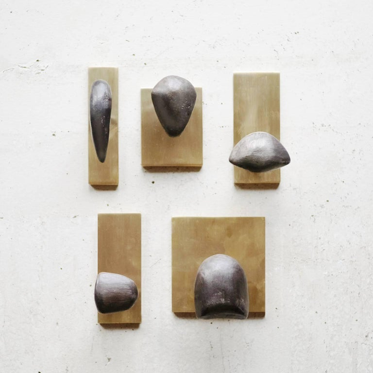 With blackened, cast brass forms soldered to a brass post and plate, the sculptural Tallomet coat hooks are a study in form and contrast. Finished by hand in Portland, Oregon, the hooks feature hidden mounting hardware and are intended to be