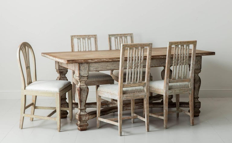 A stunning set of four 18th century Swedish dining chairs from the Gustavian period, hand-scraped to original paint. This is a beautiful set of period chairs with open-work, splat backs and straight, tapered legs with cross stretchers. Blue-green
