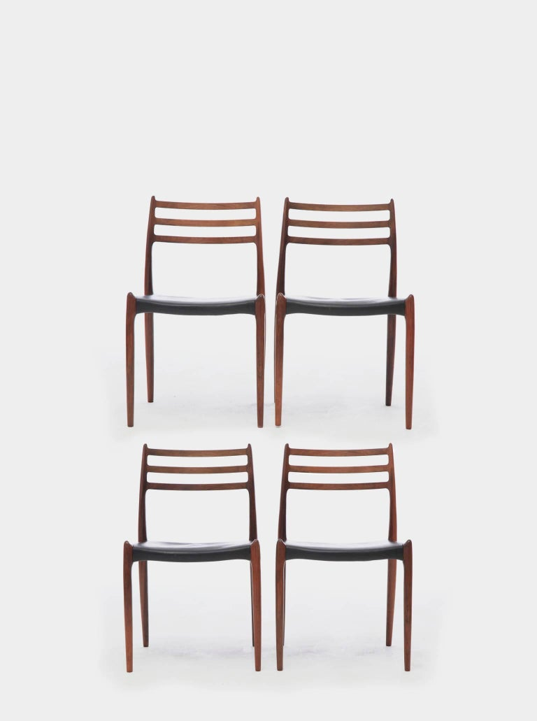 A set of four rosewood N.O. Møller 78 side chairs, 1962 for J.L. Møllers Møbelfabrik, Denmark. Rosewood, leather seat covers.