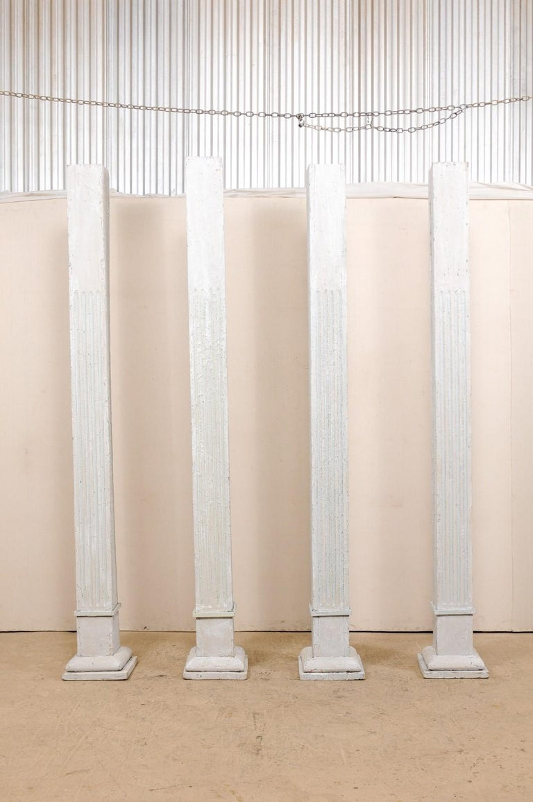 A tall set of four 19th century painted wood columns. This set of antique American pillars, standing over 8.5 feet in height, have square-shaped bodies with carved fluting, and are raised upon graduated and square-shaped bases. The columns are