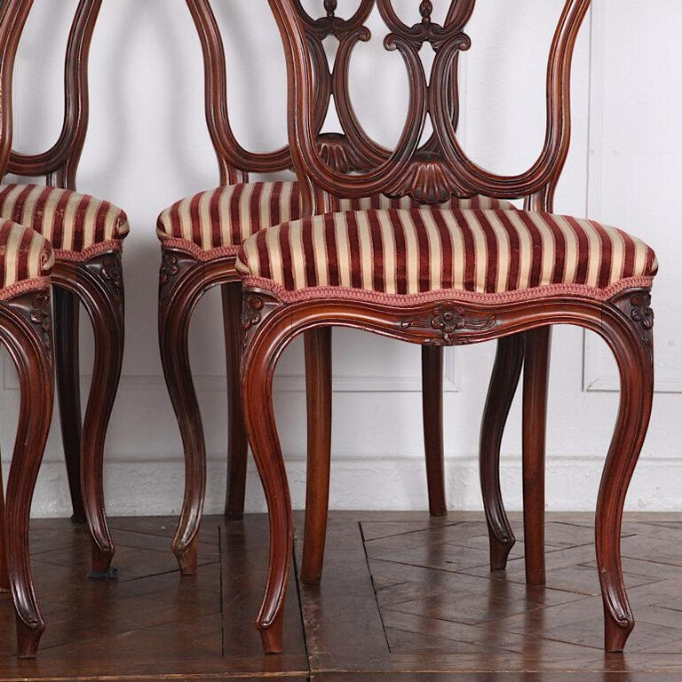 Set of four smaller-scale 19th century French chairs with elegant cabriole legs and finely shaped and pierce-carved backs. Although these are smaller chairs, they are extremely comfortable with just the right curve and angle to their backs.