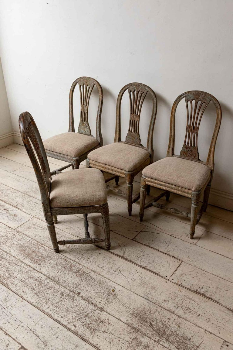 Set of four 19th century antique hand painted Swedish dining or hallway chairs with feature wheat-sheaf decoration in the central section of their backs. The chairs have scrolled detailed legs which are connected at either side and in the middle for