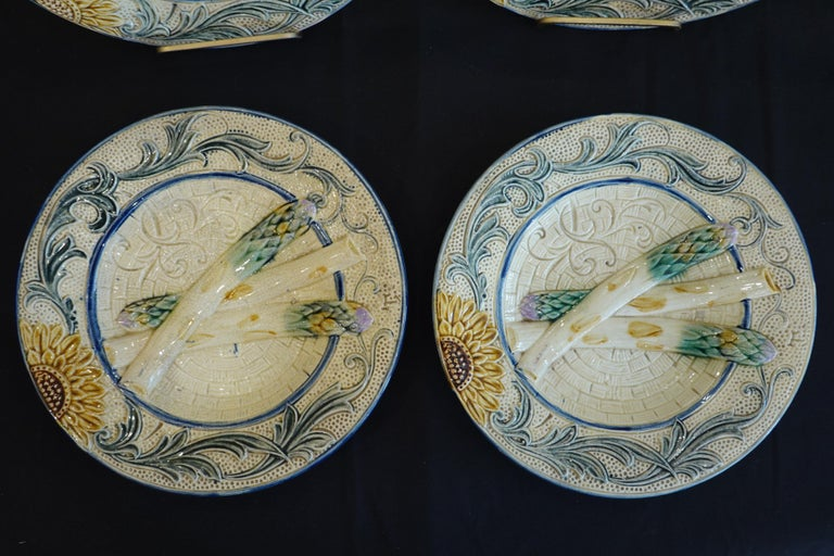 Set of four 19th century Majolica asparagus plates. Each plate features three molded asparagus spears with a sunflower and vines encircling the perimeter. The plates are unmarked, but some have an impressed letter and/or underglaze mark on the
