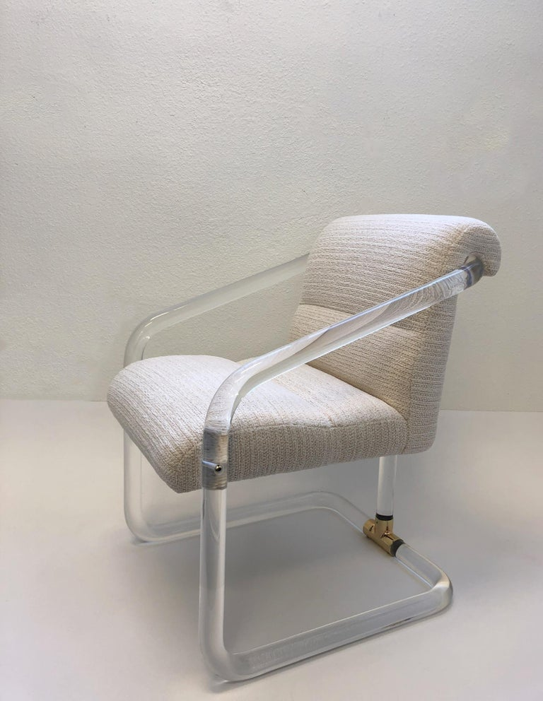 A glamorous set of four 1970s clear acrylic and polish brass arm chairs by Lion in Frost. This chair have been newly professionally polished and recovered in a beautiful off white channel fabric. All four chairs are signed Lion in