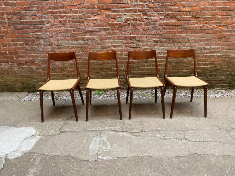 Set of four solid teak Danish modern Boomerang chairs designed by Alfred Christensen. Sculptural and ergonomically built for maximum comfort. A great chair with great lines and subtle details; box joint dovetailing, tapered legs and stretchers and