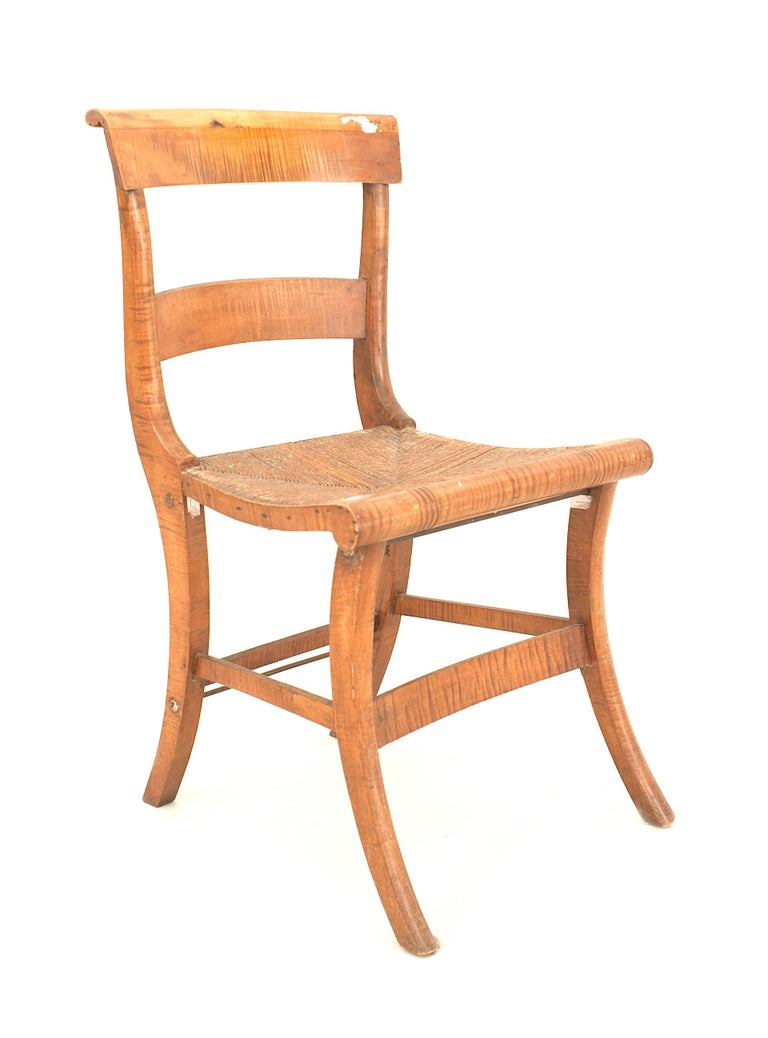 Set of four American country federal style (19th century) tiger maple side chairs with a stretcher and rush seat.
