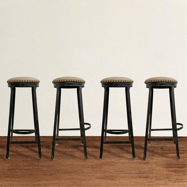 A smart set of four vintage American Industrial iron bar stools with foot rests, bent-stock feet, and newly upholstered in a beautiful taupe leather with brass nailhead trip.