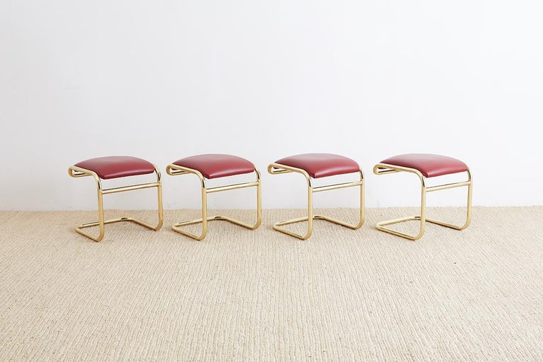 Red and gold set of four cantilever stools or ottomans designed by Anton Lorenz and produced by Thonet. Interesting modern interpretation of the German Bauhaus design featuring a gold anodized, chrome steel cantilever frame upholstered in a red