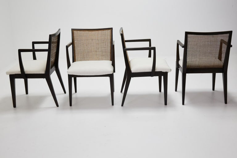 Set of four dining armchairs, model no. 5954 designed by Edward Wormley for Dunbar. Stained oak frames retain original caned backs. Seats have been reupholstered in muslin and ready for your specific fabric choice. Chairs retain brass Dunbar label
