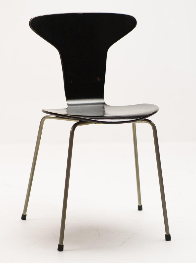 Elegant design by Arne Jacobsen, also known as Mosquito chair. This is the desirable early production with metal cap at the bottom and matte nickel-plated steel frame, black lacquered plywood in beautiful original vintage condition.