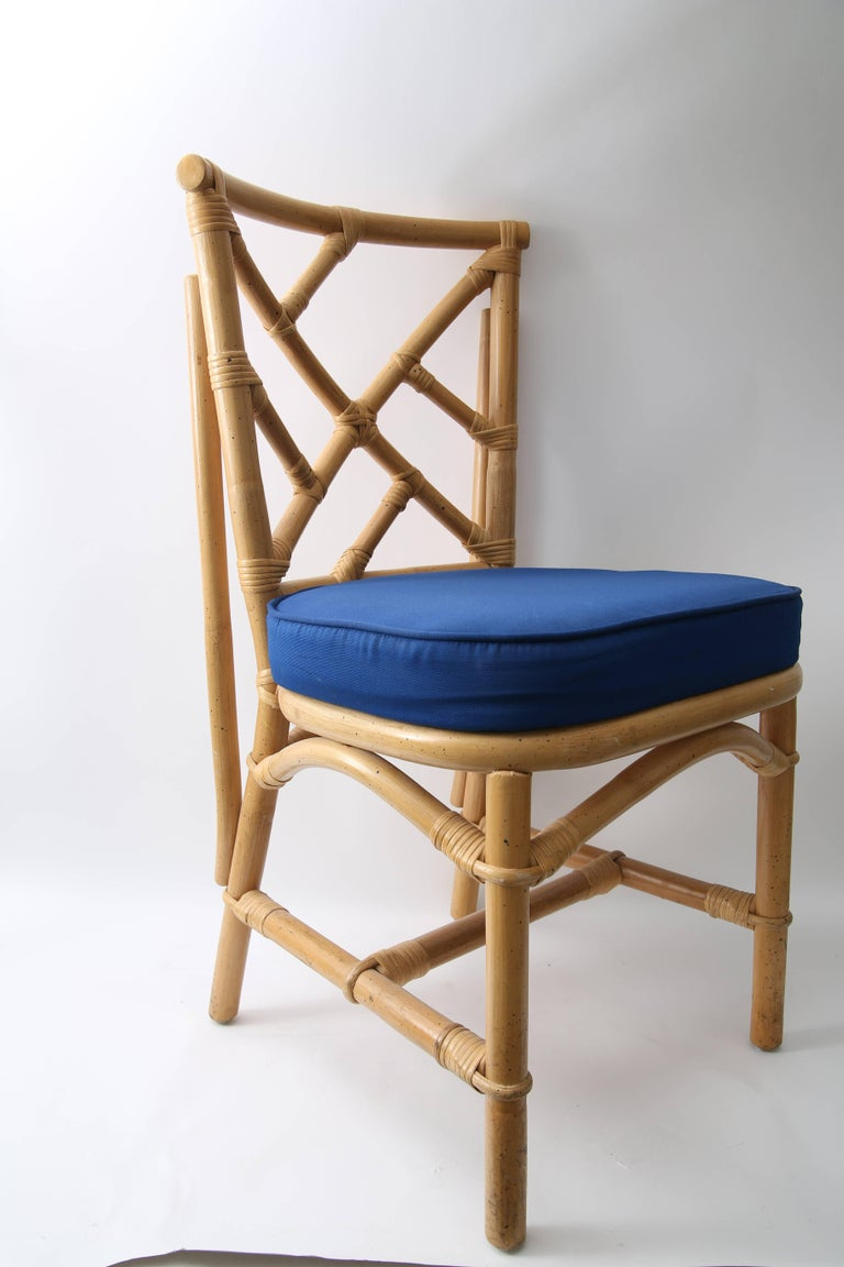 This stylish set of four side chairs are fabricated in bamboo with a fret-work Chippendale pattern and upholstered in a marine blue woven fabric.